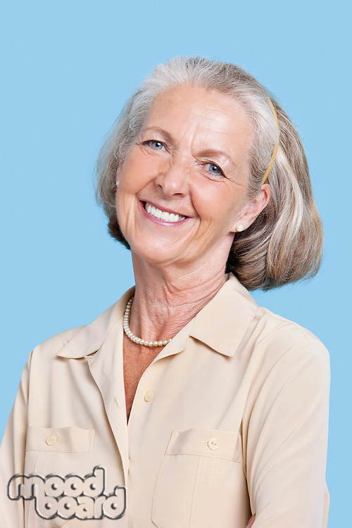 Portrait of smiling senior woman in casuals against blue background