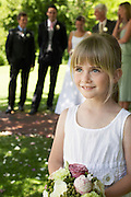 Young girl holding bouquet bride and groom in background