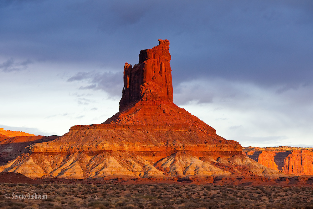 The rugged canyons, sandstone spires and mesas of Canyonlands National Park are lit orange by a setting sun after a rainstorm as seen from The White Rim Trail near Moab, Utah. The canyons have been cut over eons by water, wind and the elements creating a rugged landscape that are a playground for adventurers and hideaways for outlaws.