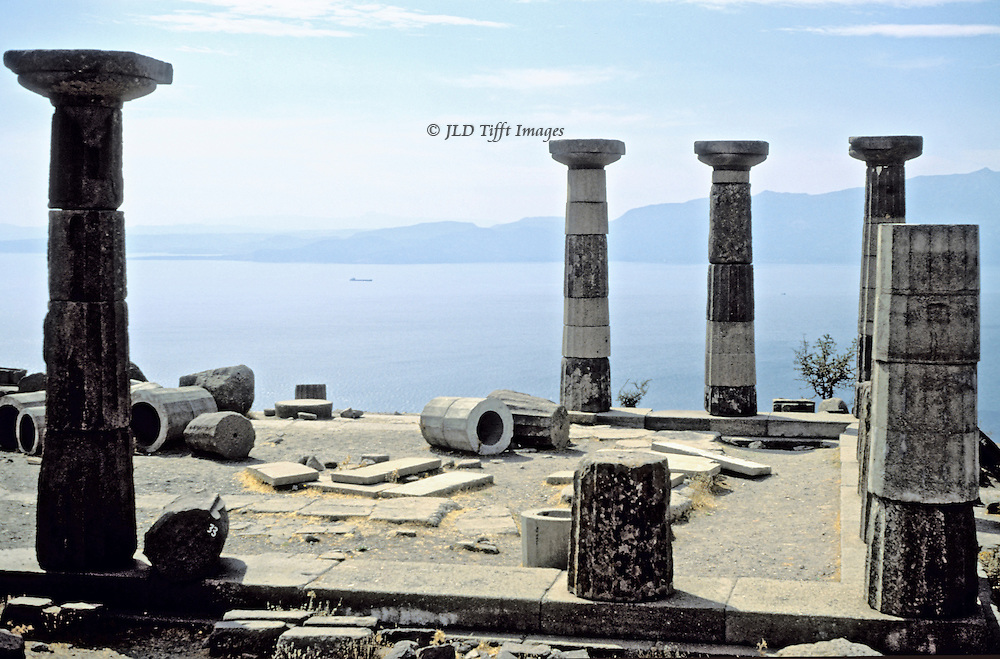 The temple of Athena after partial reconstruction first during the 1980s and a more technically proficient reconstruction during 2008.  View across the temple area, marked by masonry laid on the ground, toward the sea and island of Lesbos.  It is a spectacular setting.
