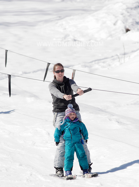 Bridgeville, New York - A woman helps a girl use the tow rope at Holiday Mountain on March  6, 2010.