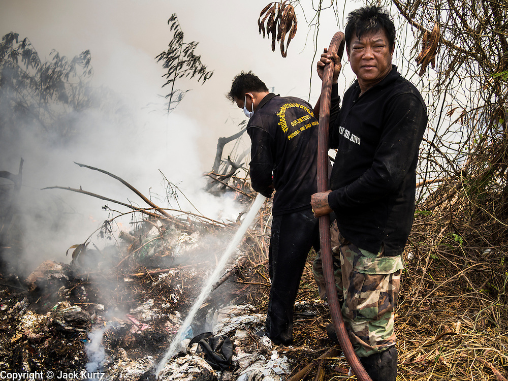 17 MARCH 2014 - PHRAEKSA, SAMUT PRAKAN, THAILAND: Firefighters try to put out a fire burning in a landfill in Samut Prakan province about 40 miles from Bangkok. The landfill is built on a bog and firefighters and volunteers battling the fire were falling through the matted vegetation into the swamp beneath. A fire apparently spontaneously started in the landfill in Samut Prakan over the weekend and threatens the homes of workers who live near the landfill. The fire Officials said the fire started when garbage in the landfill burst into flames and the flames were spread by hot, dry winds. Hundreds of people have been evacuated because of the fire and acrid smoke from the fire has spread as far as Bangkok. It hasn't rained in central Thailand in more than three months, impacting agriculture and domestic water use. Many farms are running short of irrigration water and salt water from the Gulf of Siam has come up the Chao Phraya River and infiltrated the water plants in Pathum Thani province that serve Bangkok.   PHOTO BY JACK KURTZ