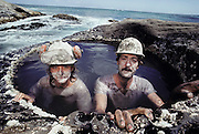 Corey Wilson and John Wilson, members of the Dinosaur Cove excavation team cool off in a rock tide pool after drilling holes in the working face of the mine to allow explosives to be placed. The explosives are used to dislodge large pieces of rock, which are then removed and checked for fossil remains. Dinosaur Cove, near Cape Otway in southern Australia, is the world's first mine developed specifically for paleo-ontological excavations. MODEL RELEASED [1989]