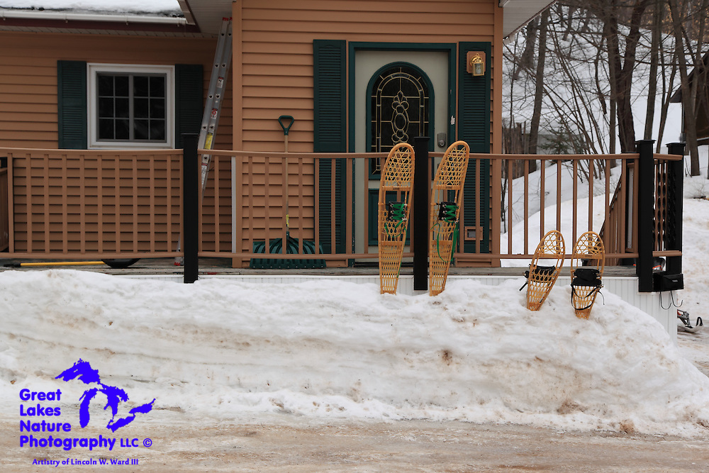 This pretty Munising home provides a look at the basic winter accoutrements for an Upper Peninsula family. These include his-and-hers snowshoes, his-and-hers snow shovels, an extension ladder for climbing up on the roof (which must be shoveled), and the barely visible snowmobile (at right) for retrieving things from the market.