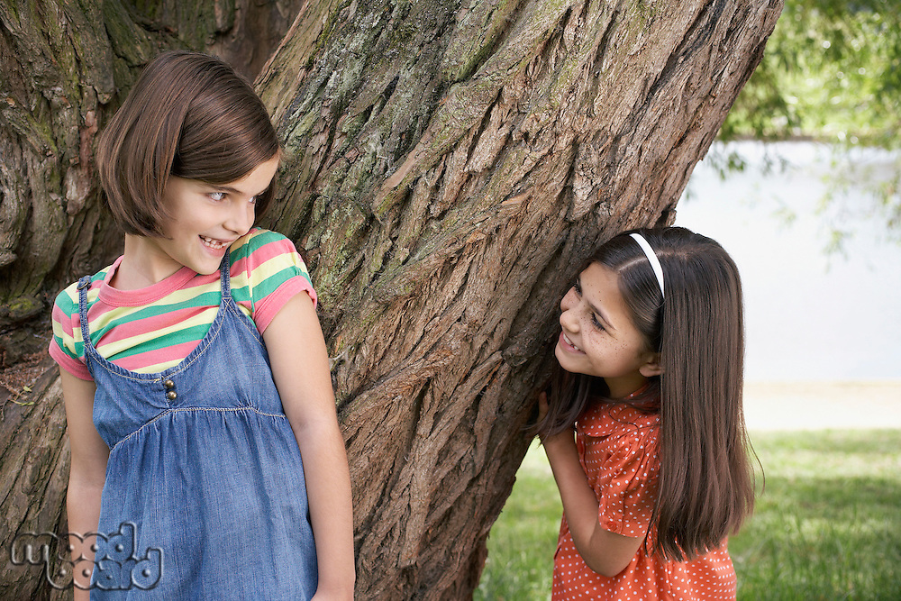 Two girls (7-9) playing hide and seek by tree