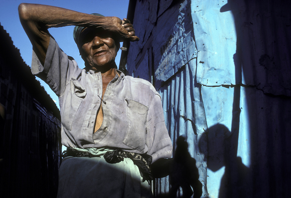Haiti, Port-au-Prince, Woman shades eyes at sunrise in Cite Soleil slum along city's coastline