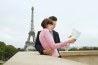 France Paris Couple reading map on balcony in front of Eiffel Tower