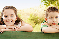 Boy (7-9) and girl (10-12) leaning against railing portrait.