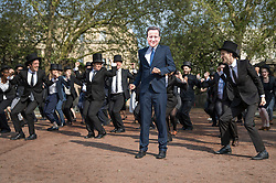 © Licensed to London News Pictures. 12/05/2016. London, UK. A protestor dressed as Prime Minister David Cameron takes part in a dance routine with others dressed as wealthy 'toff' outside the anti-corruption summit. The real Mr Cameron is hosting a one day summit which is addressing world corruption. Photo credit: Peter Macdiarmid/LNP