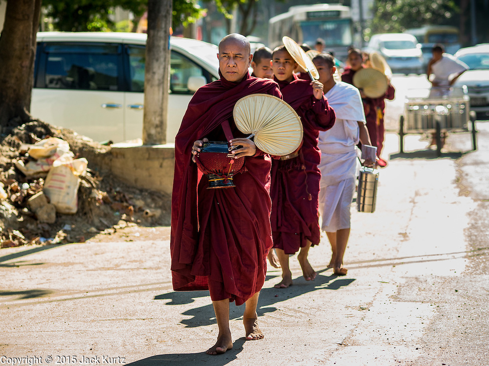 04 NOVEMBER 2015 - YANGON, MYANMAR:  Buddhist monks on the morning alms round in Yangon, Myanmar.       PHOTO BY JACK KURTZ