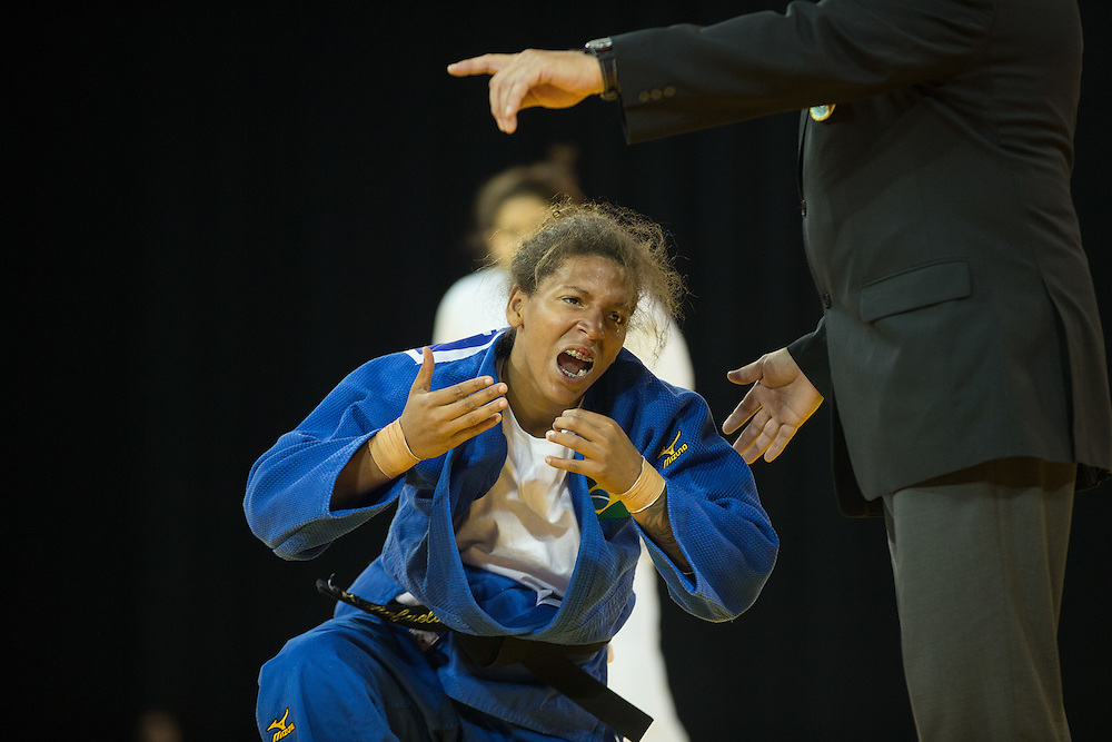 The official instructs a bloodied Rafaela Silva of Brazil to seek medical attention during her bronze medal win over Anriquelis Barrios of Venezuela in the women's judo 57kg class at the 2015 Pan American Games in Toronto, Canada, July 12,  2015.  AFP PHOTO/GEOFF ROBINS