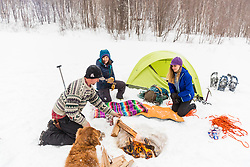 Friends enjoy a campfire while winter camping in New Hampshire's White Mountains. Randolph Community Forest.
