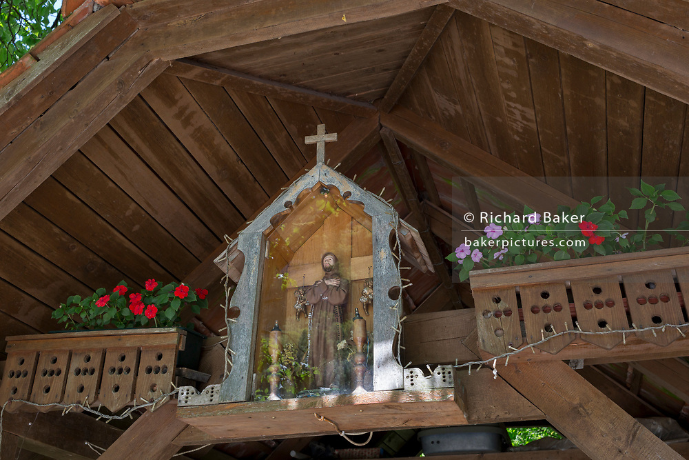 A Christian shrine in the roof of a rural village barn, on 18th June 2018, in Kupljenik, Slovenia