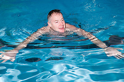 Man swimming in the pool at his local leisure centre,