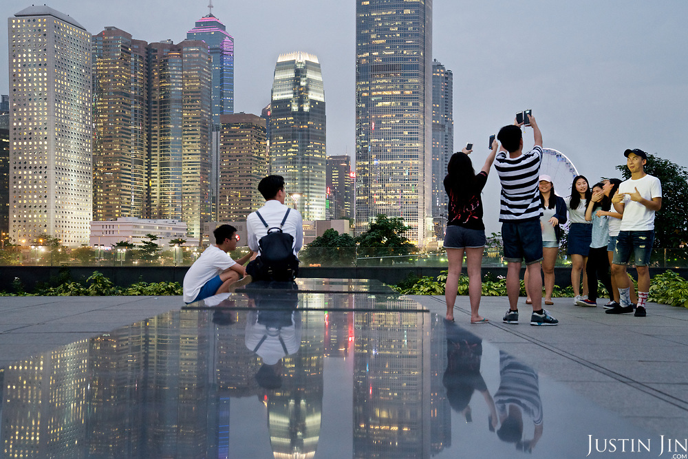 Youngsters take photographs in front of Hong Kong's Central financial district.