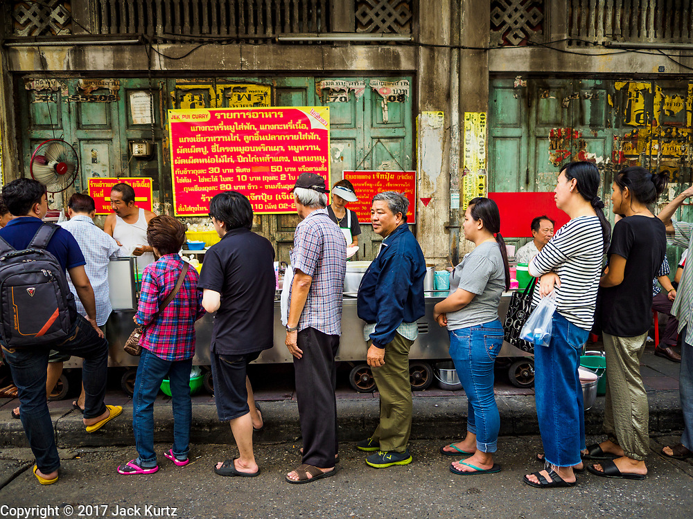 "18 MAY 2017 - BANGKOK, THAILAND: Customers stand in line fresh curries at Jek Pui curry stand, one of the most popular street food stalls in Bangkok. City officials in Bangkok have taken steps to rein in street food vendors. The steps were originally reported as a ""ban"" on street food, but after an uproar in local and international news outlets, city officials said street food vendors wouldn't be banned but would be regulated, undergo health inspections and be restricted to certain hours on major streets. On Yaowarat Road, in the heart of Bangkok's touristy Chinatown, the city has closed some traffic lanes to facilitate the vendors. But in other parts of the city, the vendors have been moved off of major streets and sidewalks.      PHOTO BY JACK KURTZ"