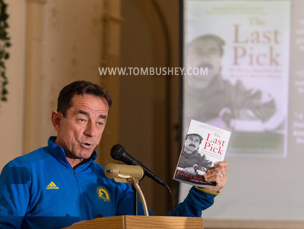 """Boston Marathon race director Dave McGillivray speaks at a special meeting of the  Orange Runners Club at Kuhl's Highland House in Middletown, New York. He is holding a copy of his book """"The Last Pick"""", which is also on the screen."""