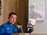 "Boston Marathon race director Dave McGillivray speaks at a special meeting of the  Orange Runners Club at Kuhl's Highland House in Middletown, New York. He is holding a copy of his book ""The Last Pick"", which is also on the screen."