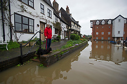© London News Pictures. 01/05/2012. Tewkesbury, UK. A woman and her dog look at flood water which is approaching houses in Tewkesbury, Gloucestershire, England on May 1, 2012. The UK has had its wettest April in over a century, with some areas seeing three times their usual average rainfall, according to figures from the Met Office. Photo credit : Ben Cawthra /LNP