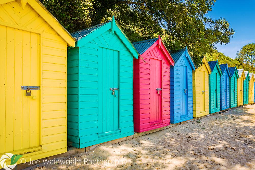 Colourful beach huts on the beach at Llanbedrog, Gwynedd, North Wales, UK.