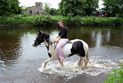 © Licensed to London News Pictures. <br /> 05/06/2014. <br /> <br /> Appleby, Cumbria, England<br /> <br /> A young girl takes her horse into the River Eden as gypsies and travellers gather during the annual horse fair on 5 June, 2014 in Appleby, Cumbria. The event remains one of the largest and oldest events in Europe and gives the opportunity for travelling communities to meet friends, celebrate their music, folklore and to buy and sell horses.<br /> <br /> The event has existed under the protection of a charter granted by King James II in 1685 and it remains the most important event in the gypsy and traveller calendar.<br /> <br /> Photo credit : Ian Forsyth/LNP