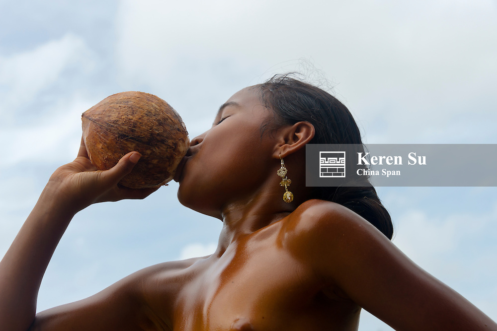 Yapese girl drinking from coconut, Yap Island, Federated States of Micronesia