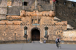 Edinburgh, Scotland, UK. 18 April 2020. Views of empty streets and members of the public outside on another Saturday during the coronavirus lockdown in Edinburgh. Man cycles past closed Edinburgh Castle. Iain Masterton/Alamy Live News
