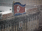 A portrait of late North Korean founder Kim Il-sung is seen under a North Korean flag as it snows in Pyongyang December 19, 2006. Photo by Lee Jae-Won (NORTH KOREA) www.leejaewonpix.com
