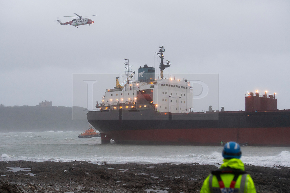 © Licensed to London News Pictures. 18/12/2018. Falmouth, UK. A member of a search and rescue team watches on as a helicopter flies over Russian cargo ship Kuzuma Minin, run aground on the reef off Gyllyngvase beach in Falmouth Bay in the early hours this morning. The Falmouth lifeboat and the Coastguard helicopter are involved in the major incident.  Photo credit: Mark Hemsworth/LNP