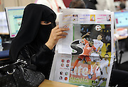 A local girl from Qatar reads an Arabic sports newspaper