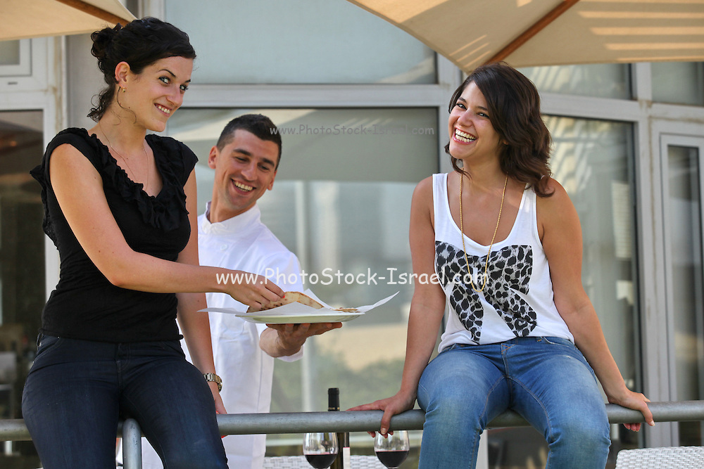 A chef serving a snack to two two female friends