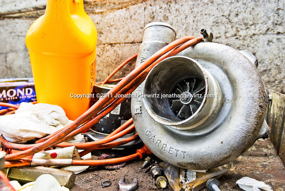 A broken turbocharger on a work bench. WATERMARKS WILL NOT APPEAR ON PRINTS OR LICENSED IMAGES.