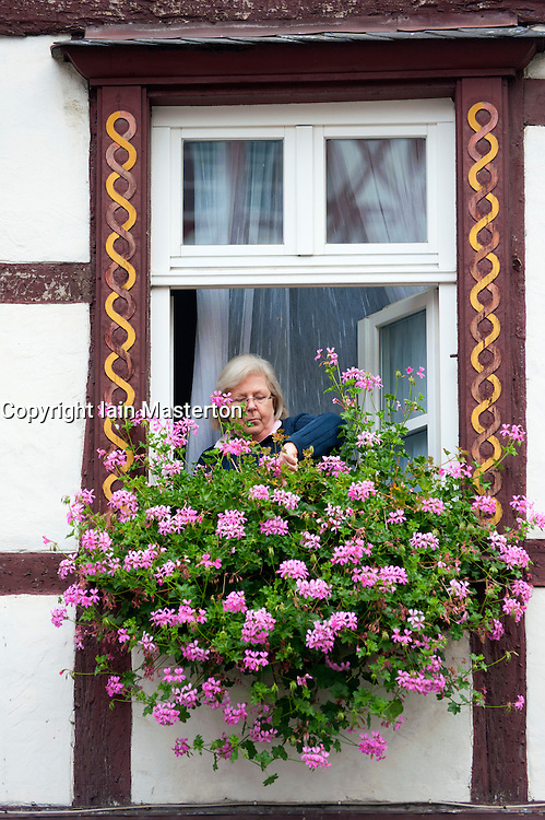 Woman tending to flower box in old half-timbered house in River Mosel in Mosel valley in Germany