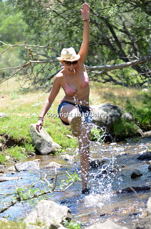 Young attractive woman having fun in mountain river