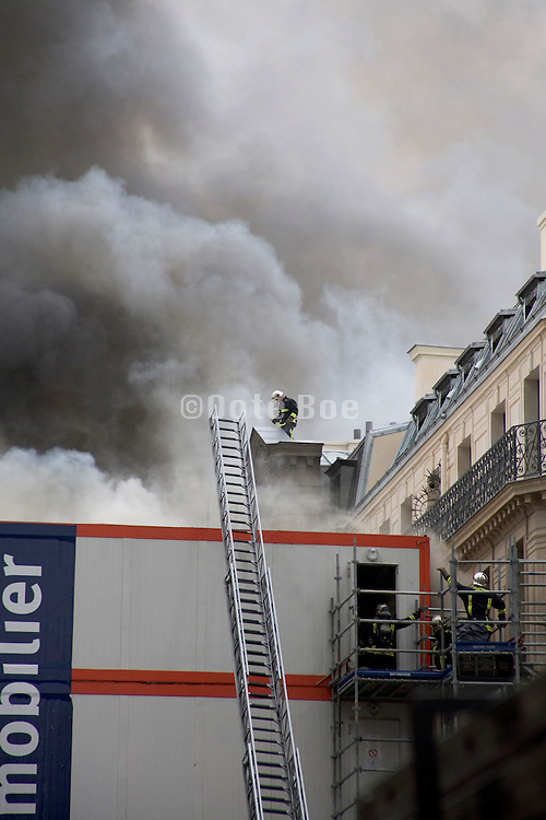 fireman on a rooftop on top of a burning building