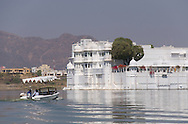 A small boat heading toward the Lake Palace Hotel on Lake Pichola in Udaipur,<br /> Rajasthan, India