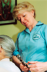 Home help in old people's home; West Yorkshire, Asian lady has her hair plaited,
