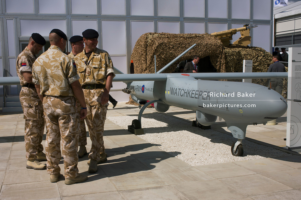 "British Army soldiers gather outside the hospitality chalet of aerospace manufacturer Thales. Standing in mid-day sun, the troops are dressed in ISAF desert uniform, alongside a company-built Watchkkeper an unmanned aerial vehicle (UAV). Watchkeeper WK450 is a £800 million contract awarded in July 2005 to Thales to provide the British Army with  or all weather, Intelligence, Surveillance, Target Acquisition and Reconnaissance (ISTAR) use. It has a weight of 450 kg and a payload capacity of 150 kg, and will have a typical endurance of 17 hours. The MoD's newest and most sophisticated surveillance and targeting drone, the Watchkeeper, is undergoing trials at Aberporth in west Wales. While the arguments over America's policy of ""assassination by drone"" rage across Pakistan and Afghanistan, fuelling public concern over the cold-eyed automation of warfare, the future of UAVs is quietly taking shape here on the Welsh coast, where there is daily proof that UAVs and manned aircraft can co-exist in British airspace."