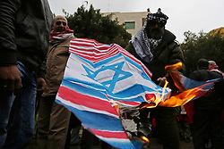 January 1, 2018 - Gaza City, Gaza Strip - Palestinians burn an Israeli flag and a U.S. flag during a protest to show solidarity with Palestinian prisoners held in Israeli jails, in front of Red cross office in Gaza city. (Credit Image: © Ashraf Amra/APA Images via ZUMA Wire)