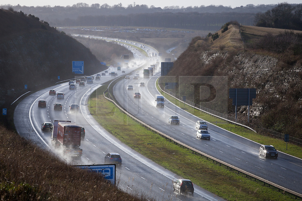 © Licensed to London News Pictures. 03/01/2014. M3, Winchester, Hampshire, UK. Vehicles lift spray into the air on a busy M3 through the Twyford Cutting near Winchester in Hampshire, UK. More wet and windy weather along with the risk of flooding is forecast for much of the south and south west of England & Wales over the weekend. Photo credit : Rob Arnold/LNP