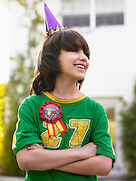 Portrait of boy (10-12) in party hat laughing arms crossed