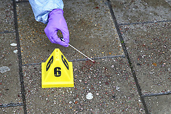 © Licensed to London News Pictures. 13/10/2019. London, UK. A forensic officer gathers blood stains as part of the evidence at the entrance of West Green Halal Meat and Groceries store on West Green Road in Tottenham, North London where two men were stabbed and rushed to hospital shortly after 9.30am this morning. The ages of the two victim and their condition is not yet know. Photo credit: Dinendra Haria/LNP