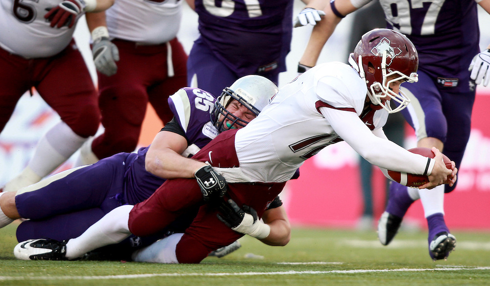McMaster Marauders quarterback Kyle Quinlan is tackled by the University of Western Ontario's David Lee during the first quarter of their OUA semi-final at TD Waterhouse Stadium in London, Ontario, November 6, 2010. Western defeated McMaster 34-28.<br /> <br /> The Canadian Press/GEOFF ROBINS