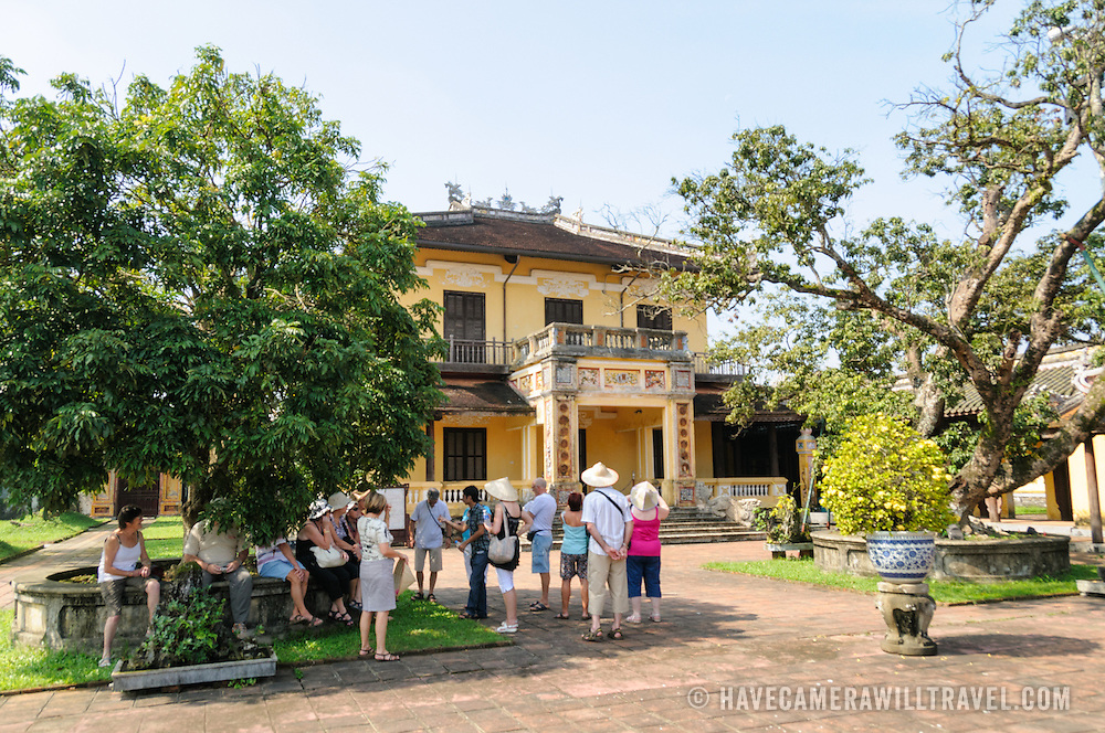 Tourists stand in the shade of a tree at the Imperial City in Hue, Vietnam. A self-enclosed and fortified palace, the complex includes the Purple Forbidden City, which was the inner sanctum of the imperial household, as well as temples, courtyards, gardens, and other buildings. Much of the Imperial City was damaged or destroyed during the Vietnam War. It is now designated as a UNESCO World Heritage site.