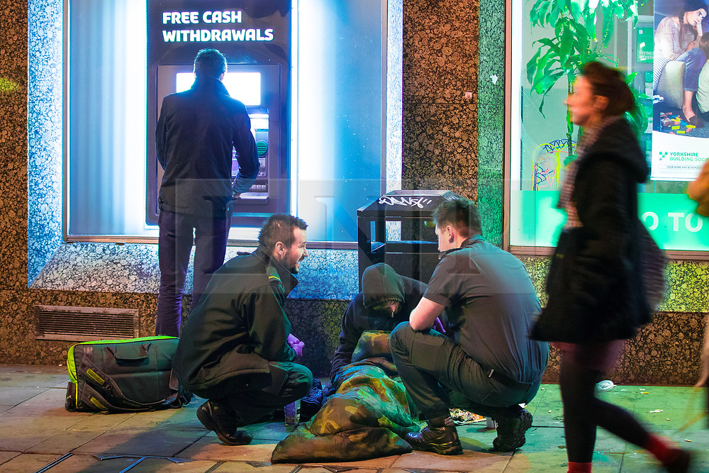© Licensed to London News Pictures . 07/04/2017 . Manchester , UK . Paramedics attend to a man who is slumped over in front of a bin by a cash dispenser in Piccadilly Gardens . Greater Manchester Police have authorised dispersal powers and say they will ban people from the city centre for 48 hours , this evening (7th April 2017) , in order to tackle alcohol and spice abuse . Photo credit : Joel Goodman/LNP