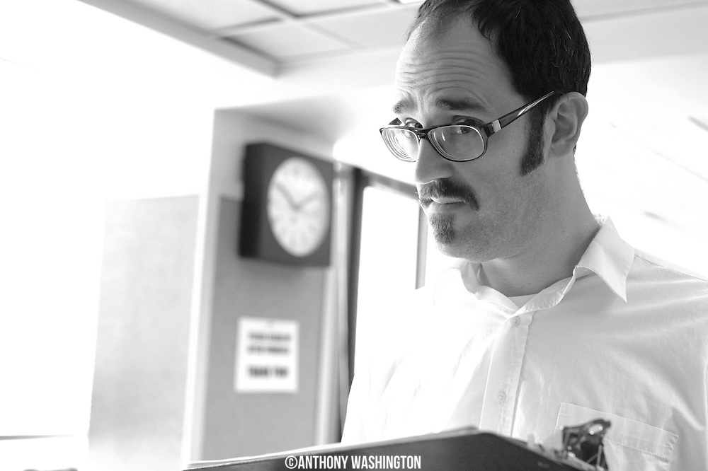 """Local Morning Edition host Matt """"Fear The Stache"""" McCleskey looks up from checking the hourly totals following his shift on Monday, February 14, 2011."""