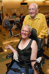 Woman wheelchair user and partner at a disability friendship club social event,