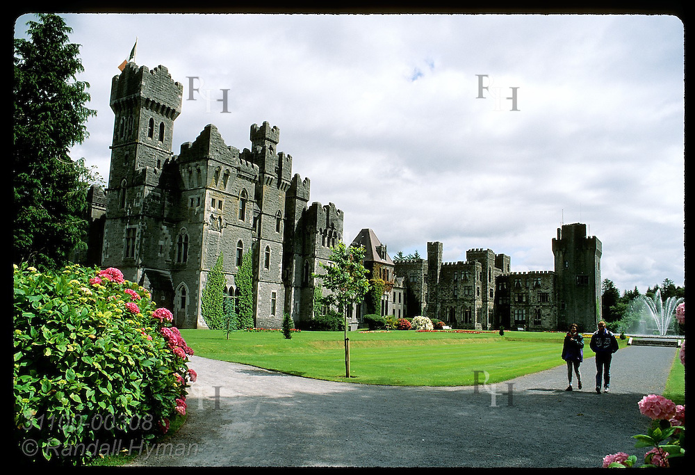 Couple walks flowered path leading from Ashford Castle, one of Ireland's finest hotels; Cong. Ireland
