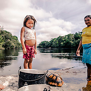 Umarituba. Mum and daughter wash and prepare to cook a turtle they hunted in the forest
