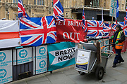 On the day that the EU in Brussels agreed in principle to extend Brexit until 31st January 2020 (aka 'Flextension') and not 31st October 2019, a Westminster borough street cleaner picks up litter next to Brexit Party flags and banners during a Brexit protest outside parliament, on 28th October 2019, in Westminster, London, England.